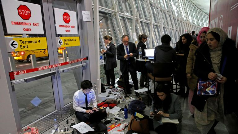 Women walk by a team of volunteer lawyers in their makeshift office working to assist detained travelers at JFK airport in Queens