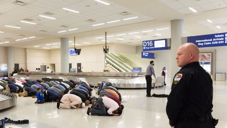 People gather to pray in baggage claim during a protest against the travel ban imposed by U.S. President Donald Trump's executive order, at Dallas/Fort Worth International Airport