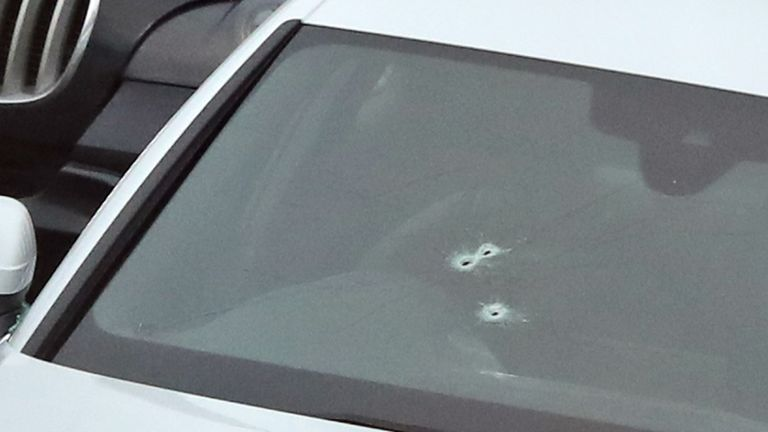 Three bullet holes can be seen in the windscreen of a silver Audi near the motorway junction