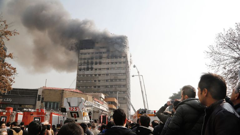 People look at the fire at the Plasco building in Tehran