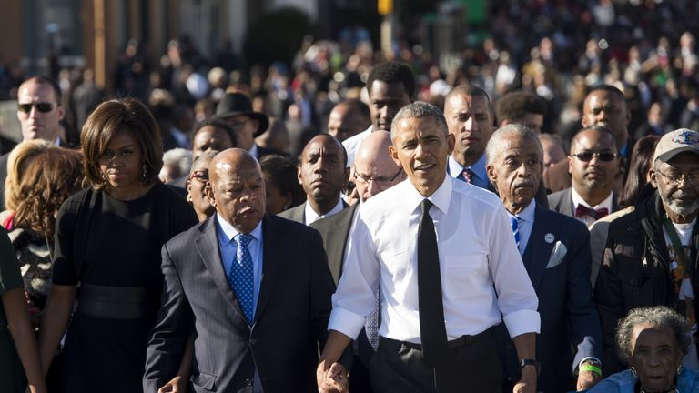 John Lewis holds hands with the Obamas on the 50th anniversary of the march in Selma