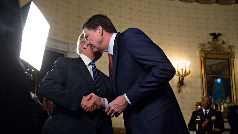 US President Donald Trump (L) shakes hands with James Comey