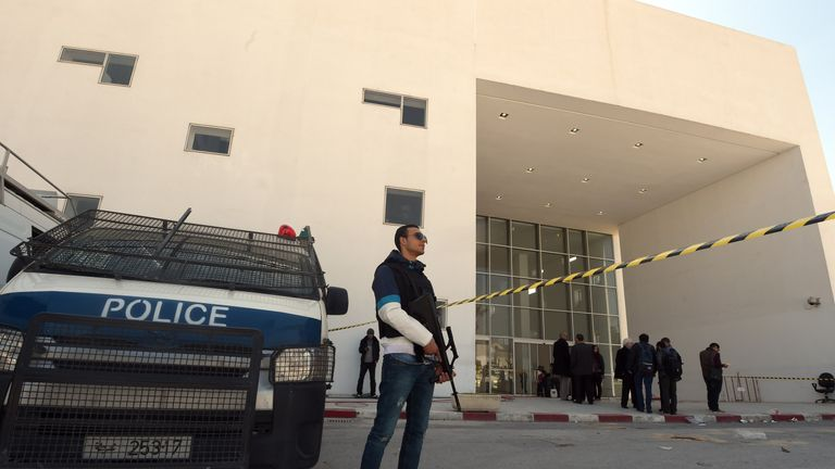 Tunisian security forces and forensic experts stand at the visitors entrance of the National Bardo Museum in Tunis on March 19, 2015, in the aftermath of an attack on foreign tourists