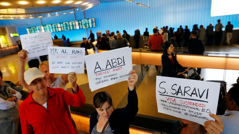 Demonstrators hold up signs with the names of people detained and denied entry in LA