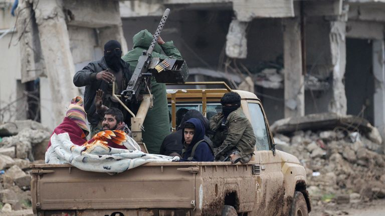 Rebel fighters ride on a pick-up truck in the northern Syrian rebel-held town of al-Rai