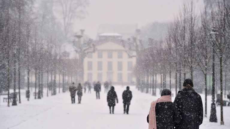 People walk in the snowfall in a park in Strasbourg, eastern France