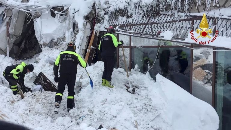 Firefighters digging through the snow at the hotel Rigopiano