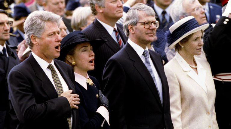Bill and Hillary Clinton sing the US national anthem alongside John  and Norma Major at the American Cemetery and Memorial in Cambridge, 1994