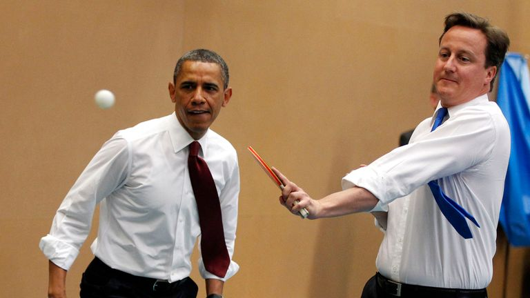 Barack Obama plays table tennis against students with David Cameron at the Globe Academy in London, 2011