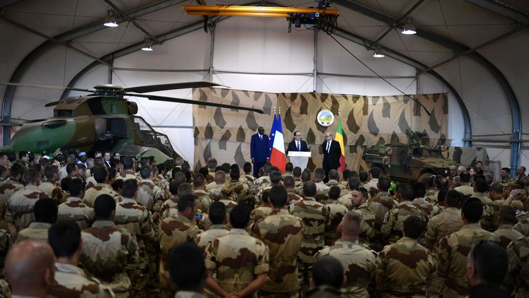 French President Francois Hollande (C) delivers a speech next to Malian Prime Minister Modibo Keita (L) and French Defence Minister Jean-Yves Le Drian (R), to the troops of France's Barkhane counter-terrorism operation in Africa's Sahel region in Gao, northern Mali on January 13, 2017