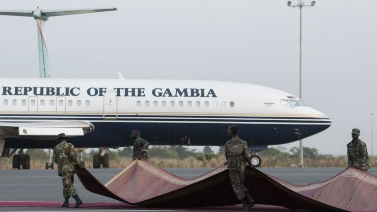 Gambian soldiers roll back a red carpet at Banjul airport