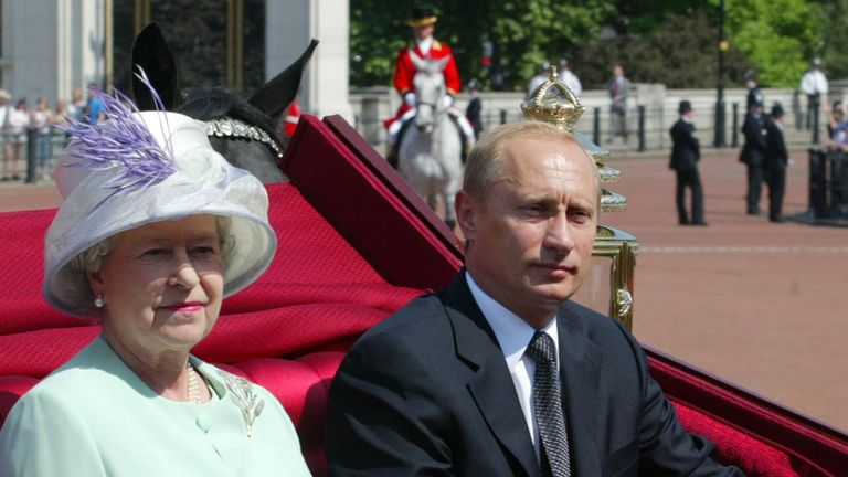 A carriage carrying Queen Elizabeth II and Russian President Vladimir Putin is escorted by royal guards to Buckingham Palace, June 24, 2003