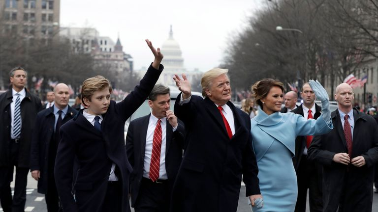 Donald Trump and his family walk down Pennsylvania Avenue to the White House