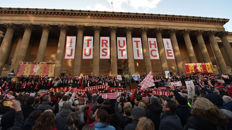 """People hold Liverpool football scarves in the air as they sing """"You'll Never Walk Alone"""" outside St George's Hall in Liverpool"""
