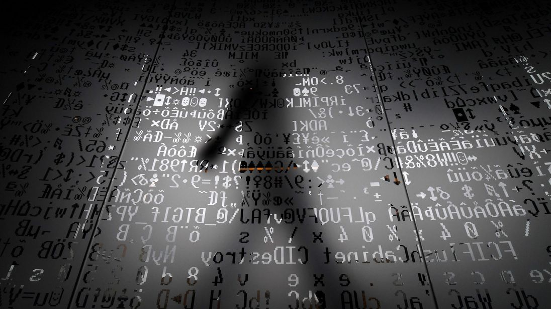 A picture taken on October 17, 2016 shows an employee walking behind a glass wall with machine coding symbols at the headquarters of Internet security giant Kaspersky in Moscow