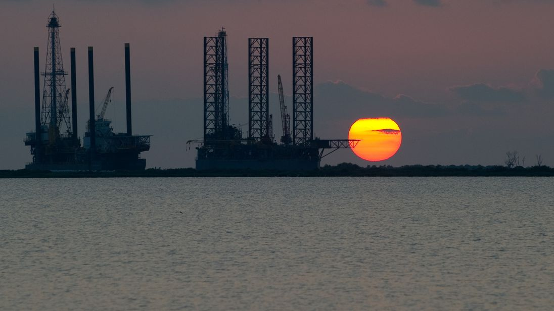 The sun sets behind two under construction offshore oil platform rigs in Port Fourchon, Louisiana, June 14, 2010, as cleanup continues on the BP Deepwater Horizon oil spill