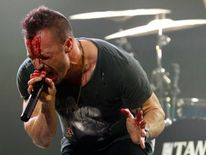 Lead singer Greg Puciato performs with a bloody face in 2013