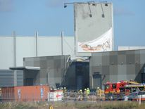 Fire crew at the scene where a light aircraft crashed into the back of Essendon airport