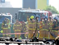 Fire crew at the scene where a light plane crashed into the back of a building at Essendon airport in Melbourne, Australia