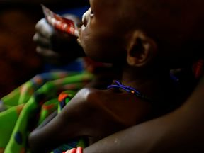 A mother feeds her child with a peanut-based paste for treatment of severe acute malnutrition