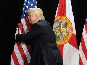 Republican presidential candidate Donald Trump hugs the American flag as he arrives for a campaign rally at the MidFlorida Credit Union Amphitheatre on October 24, 2016 in Tampa, Florida