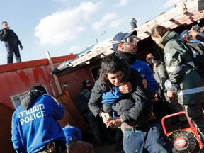 A police officer carries an Israeli boy during an operation to evict occupants from the West Bank settler outpost of Amona after a court ruled homes were built on Palestinian land