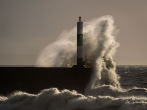 The lighthouse and harbour wall is battered by waves at Aberystwyth, Wales, as flights have been cancelled and commuters were warned they faced delays after Storm Doris reached nearly 90mph on its way to batter Britain
