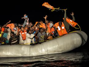 Rescue workers throw lifejackets to migrants and refugees off the coast of Libya