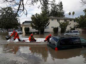 Firefighters search for victims in the floods in San Jose