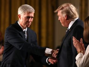 Judge Neil Gorsuch (L) shakes hands with U.S. President Donald Trump as Gorsuch's wife Louise (R) applauds after President Trump nominated Gorsuch to be an associate justice of the U.S. Supreme Court at the White House in Washington