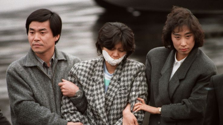 North Korean agent Kim Hyon-Hee is flanked by South Korean investigators as she arrives in Seoul in December 1987