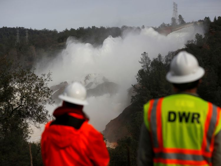 Staff with the California Department of Water Resources watch as water is released from the Lake Oroville Dam after an evacuation was ordered for communities downstream from the dam in Oroville, California, U.S., February 13, 2017