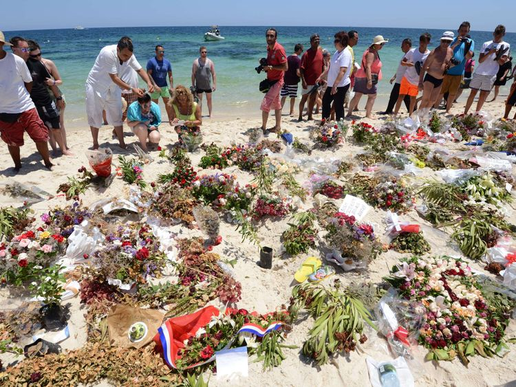Tourists and Tunisians take part in a ceremony on July 3, 2015, in memory of those killed the previous week by a jihadist gunman in front of the Riu Imperial Marhaba Hotel in Port el Kantaoui, on the outskirts of Sousse south of the capital Tunis. Tunisia has arrested eight people in connection with last week's jihadist massacre at the seaside resort, as the remains of more slain Britons were flown home on July 2