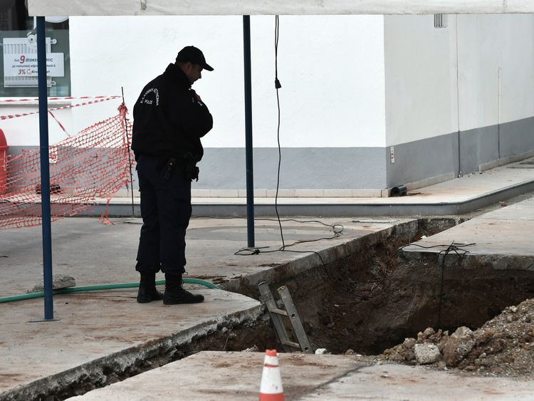 A police officer looks at the hole where the unexploded shell was found by workmen