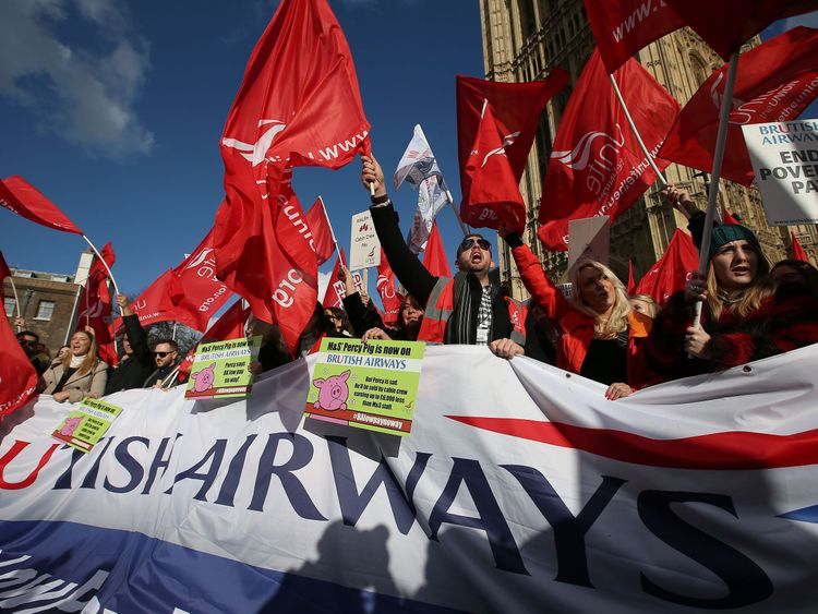 Demonstrators hold placards and wave flags as they protest against the low wages and 'poverty pay' of British Airways' staff, outside the Houses of Parliament in London on February 7, 2017. The trade union Unite claims British Airways cabin crew are on 'poverty' pay, with many forced to take on second jobs or turn up for shifts if they are sick because they cannot afford to be off ill. Another three-day strike is set to start on Thursday
