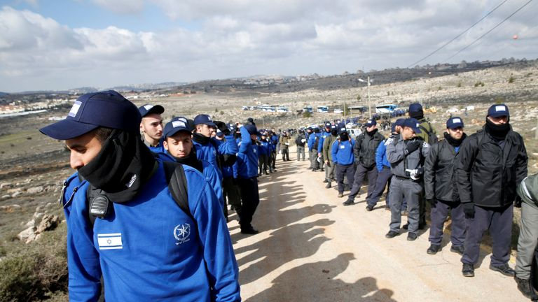 Israeli policemen line up as they prepare to evict residents of the Israeli settler outpost of Amona