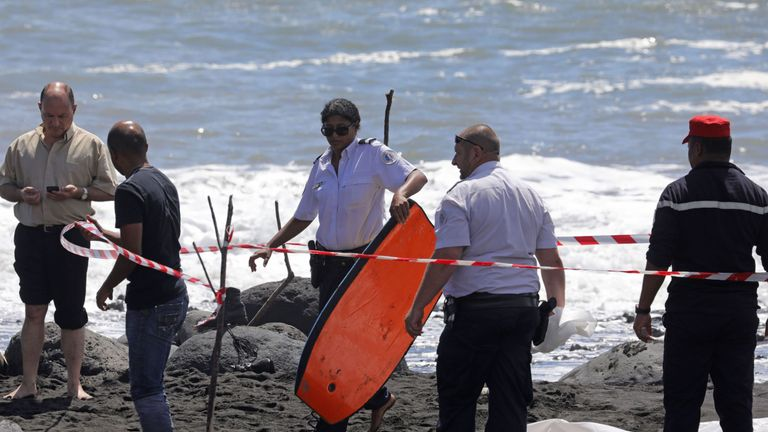 A policewoman holds the bodyboard of a bodyboarder killed by a shark