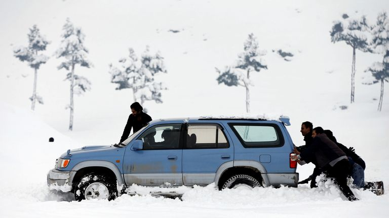 Afghan men push a car which stuck in the snow