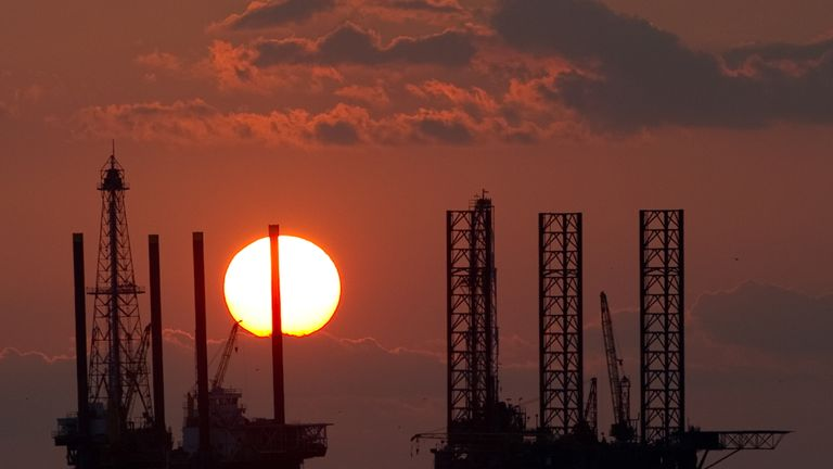 The sun sets behind two under construction offshore oil platform rigs in Port Fourchon, Louisiana, June 14, 2010, as cleanup continues on the BP Deepwater Horizon oil spil