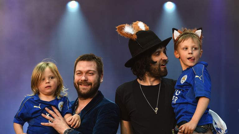Kasabian and their children wave to the fans at the Leicester City bus parade