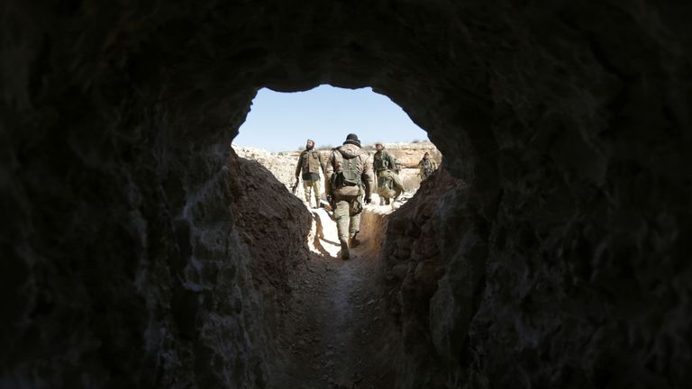 Rebel fighters walk out from a cave that was used by Islamic State militants, after they captured the area from them, on the outskirts of al-Bab