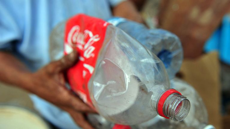 A man in Nicaragua reclaims plastic coke bottles from landfill to sell for recycling