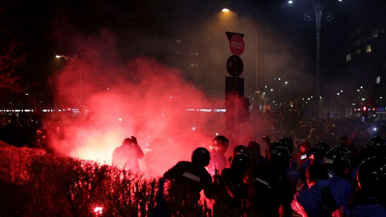 Flare thrown by protesters lands near Romanian police during scuffles at a protest in Bucharest