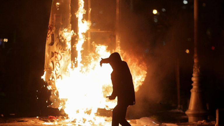 A protester walks in front of a burning street sign