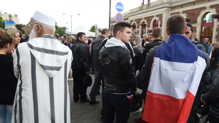 A man wearing a French flag stands next to a man wearing a Muslim clothing as people gather outside the railway station in Mantes-la-Jolie on June 18, 2016, to take part in a march in tribute to French policeman Jean-Baptiste Salvaing and his partner Jessica Schneider who were killed outside their home in Magnanville, by a convicted extremist who had pledged allegiance to the Islamic State group