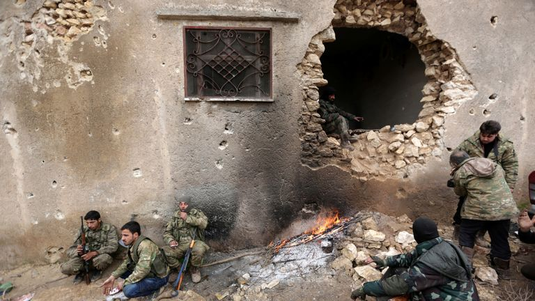 Rebel fighters rest near a hole in the wall by a fire on the outskirts of the northern Syrian town of al-Bab
