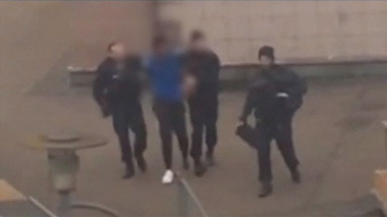 Police lead away the suspect after the assault allegedly took place