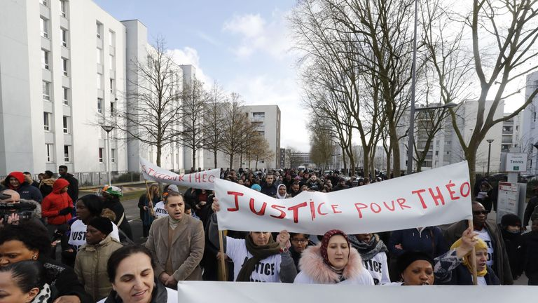 Marchers carry placards in protest at the alleged assault of a black man in a Paris suburb