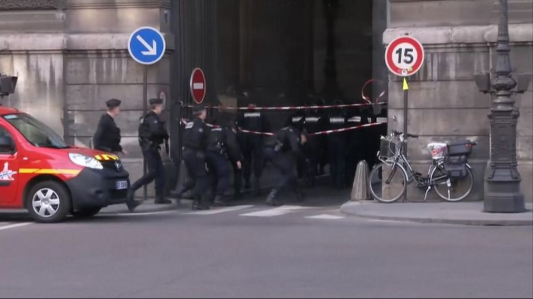 Armed police rush towards an entrance to the museum