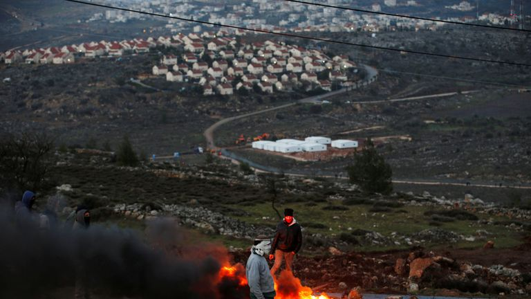 Protesters burn tyres at the entrance to the Israeli settler outpost of Amona